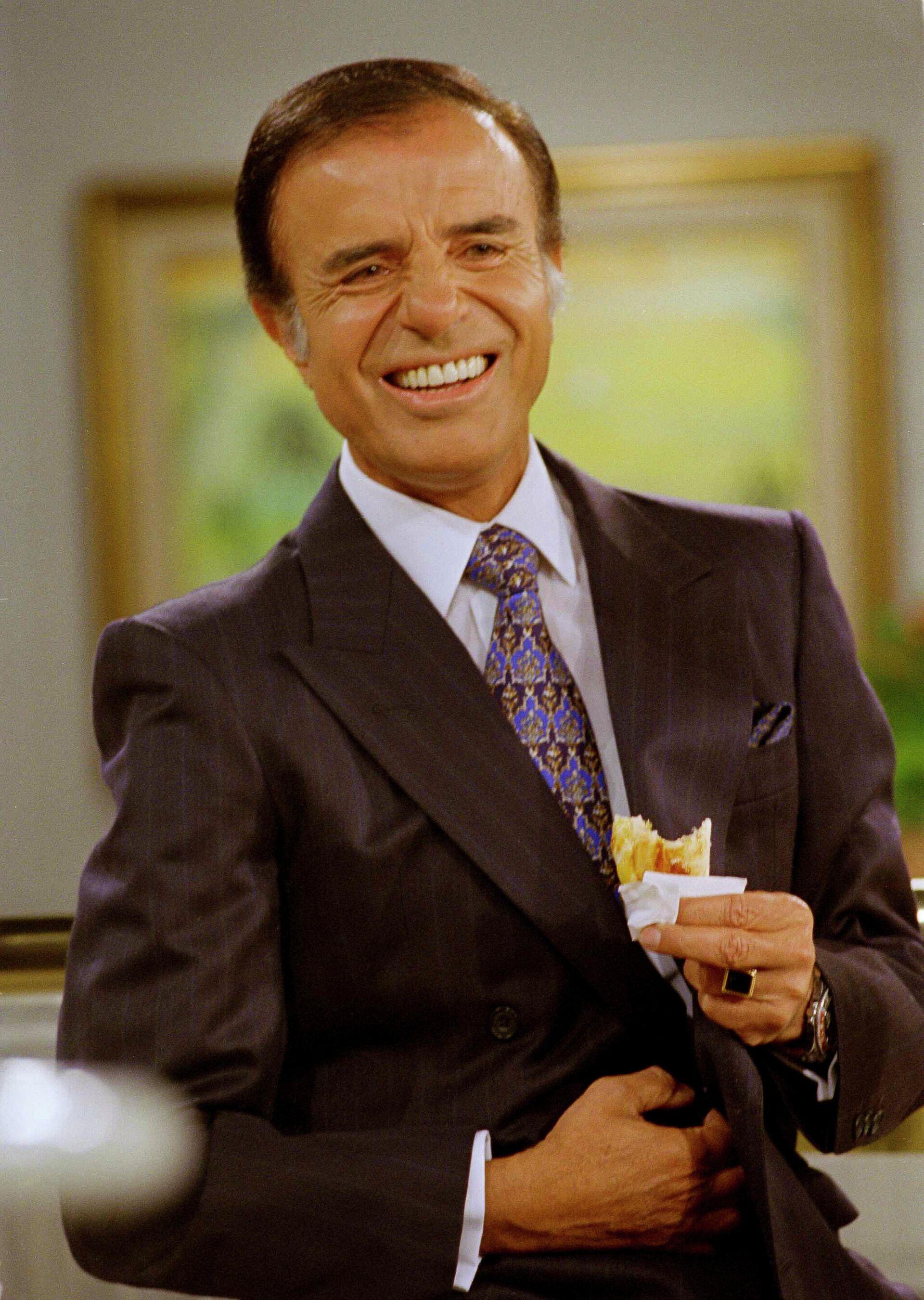 Carlos Menem , con su anillo de oro, comiendo una empanada en un programa de televisión en 1995 - Sputnik Mundo, 1920, 17.02.2021