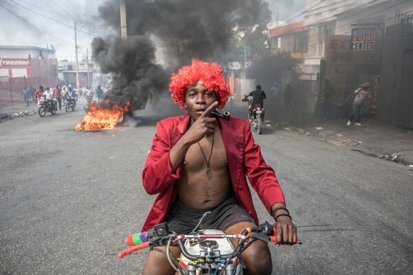 Los manifestantes marchan en Puerto Príncipe el 14 de febrero de 2021 para protestar contra el Gobierno del presidente Jovenel Moise. Varios miles de personas se manifestaron diciendo que el Gobierno estaba tratando de establecer una nueva dictadura y denunciaron el apoyo internacional al presidente Jovenel Moise. Las protestas fueron en su mayoría pacíficas, aunque se produjeron algunos enfrentamientos entre manifestantes y la Policía, que lanzó gases lacrimógenos y balas de goma. - Sputnik Mundo