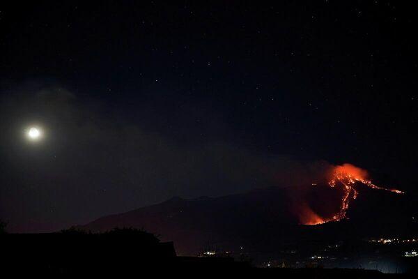 El volcán más activo de Europa, el Etna, entra en erupción con sus corrientes de lava al rojo vivo y cubre el cielo nocturno de la ciudad italiana de Giarre, región de Sicilia, el 16 de febrero.  - Sputnik Mundo