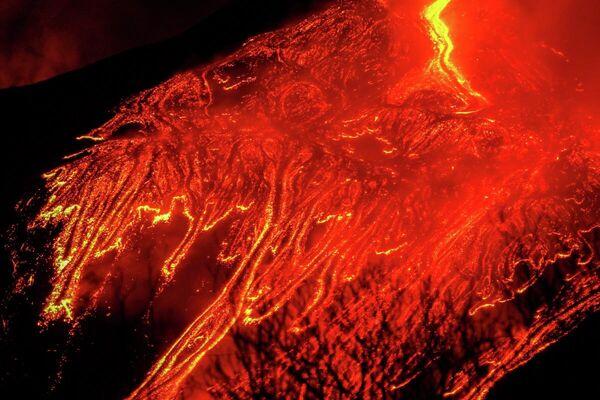 El Etna continúa en erupción con sus enormes corrientes de lava al rojo vivo y cubre el cielo nocturno del pueblo italiano de Fornazzo, el 23 de febrero. - Sputnik Mundo