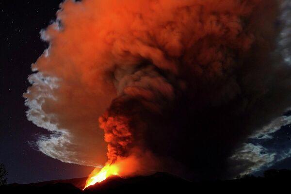 Enormes corrientes de lava al rojo vivo del Etna se lanzan al cielo nocturno de Italia. El volcán arrojó una enorme columna de humo y cenizas de más de un kilómetro de altura. - Sputnik Mundo