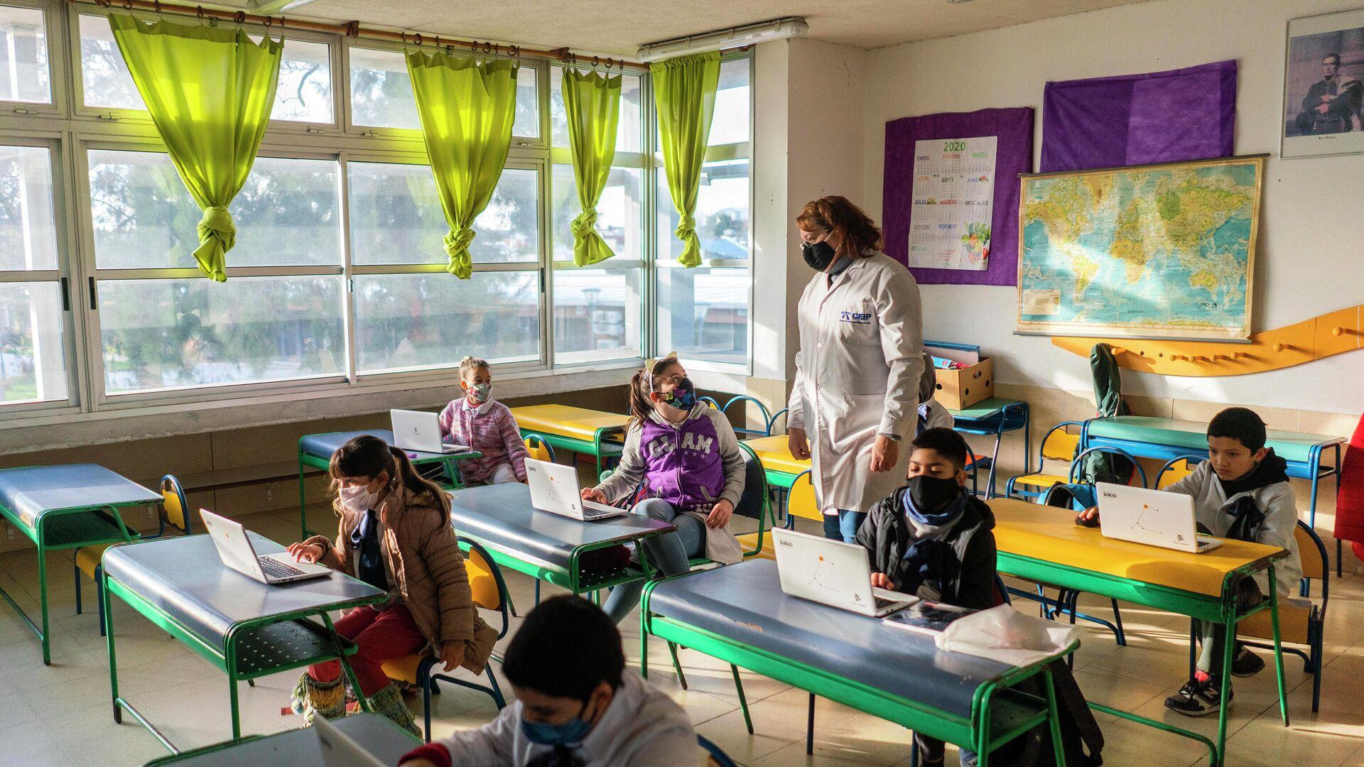 Niños utilizando mascarilla dentro de un salón de una escuela de Montevideo, durante el año 2020 - Sputnik Mundo, 1920, 24.02.2021