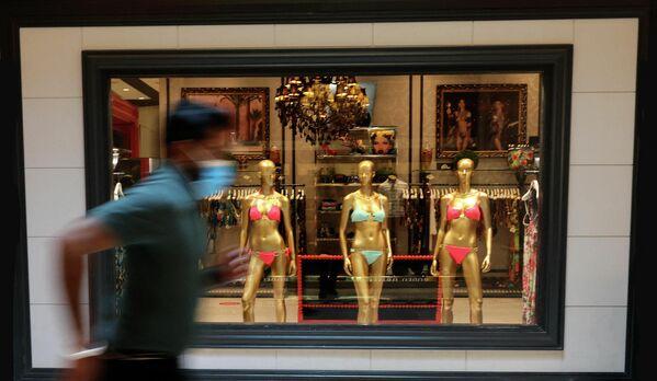 Un hombre pasa frente a la vitrina de una tienda en la isla Palma Jumeirah en Emiratos Árabes Unidos. - Sputnik Mundo