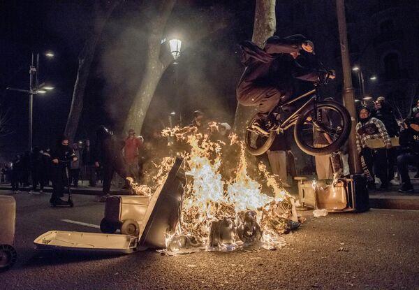 Un ciclista salta sobre los restos de una barricada en llamas tras una manifestación en apoyo al rapero Pablo Hasél en Barcelona, España. - Sputnik Mundo