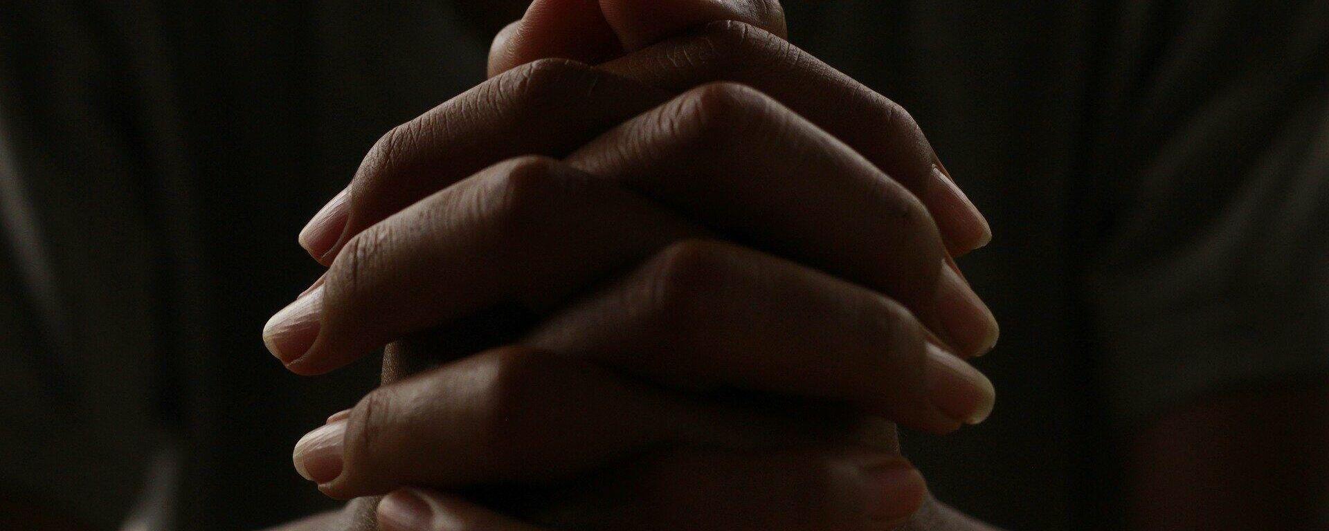 Una persona rezando con las manos entrelazadas - Sputnik Mundo, 1920, 03.03.2021
