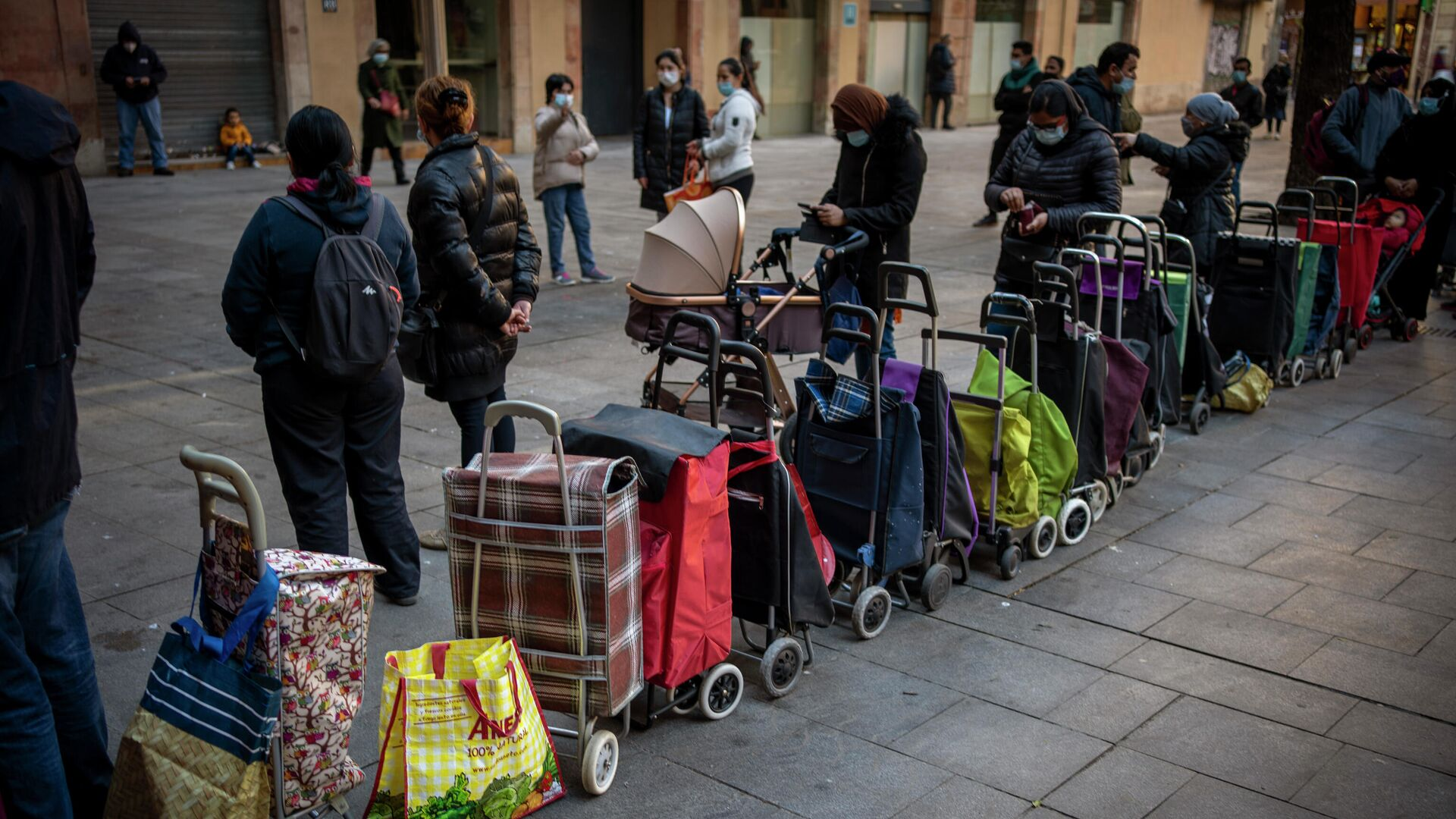 Carritos de compras alineados junto a sus dueños, esperando su turno para recibir un paquete semanal de alimentos y suministros donados, afuera de una iglesia en Barcelona, España, el miércoles 3 de febrero de 2021. - Sputnik Mundo, 1920, 06.04.2021