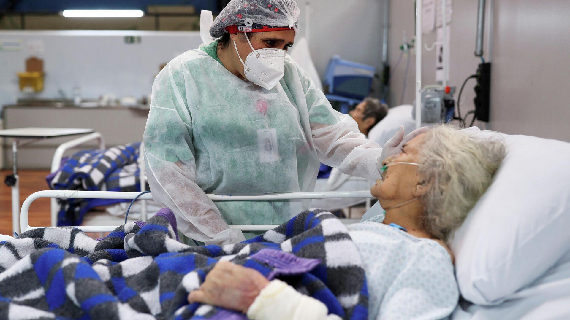 Una enfermera atienda a una mujer de 80 años en el hospital Santo Andre, en Sao Paulo - Sputnik Mundo, 1920, 22.03.2021