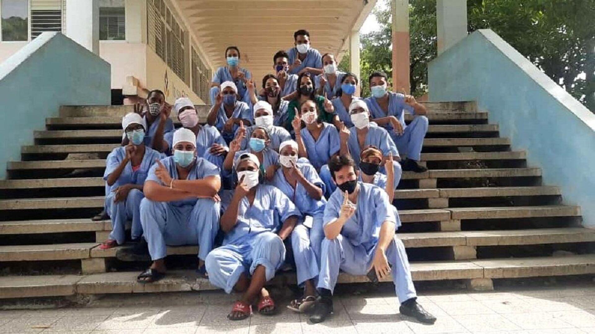 Jóvenes voluntarios cubanos en centro de aislamiento como personal de apoyo. El gesto con el dedo indica Primer PCR negativo - Sputnik Mundo, 1920, 04.03.2021