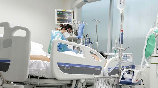 Una enfermera atiende a un paciente con COVID-19 en Chile - Sputnik Mundo