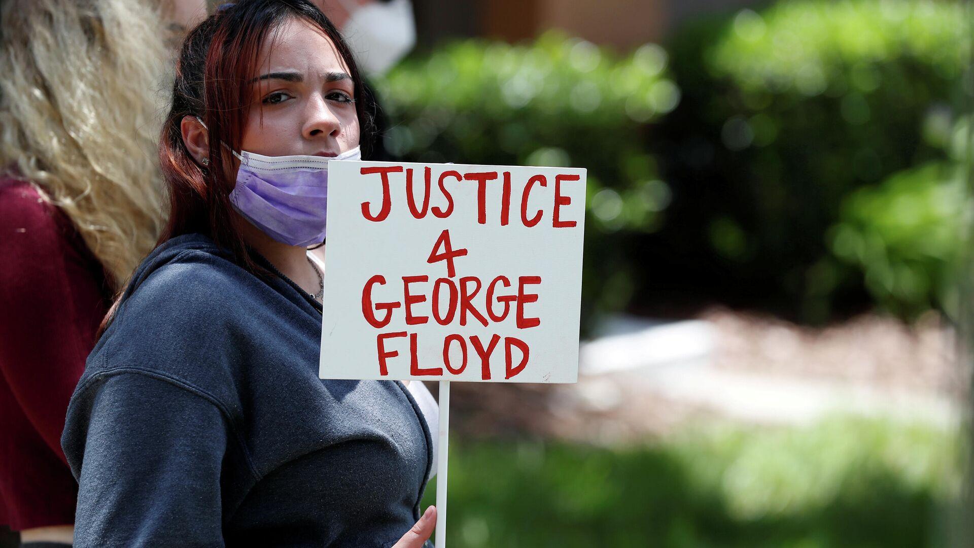 Un manifestante sostiene un cartel que dice Justicia para George Floyd cerca de la casa del exoficial de policía Derek Chauvin - Sputnik Mundo, 1920, 07.03.2021