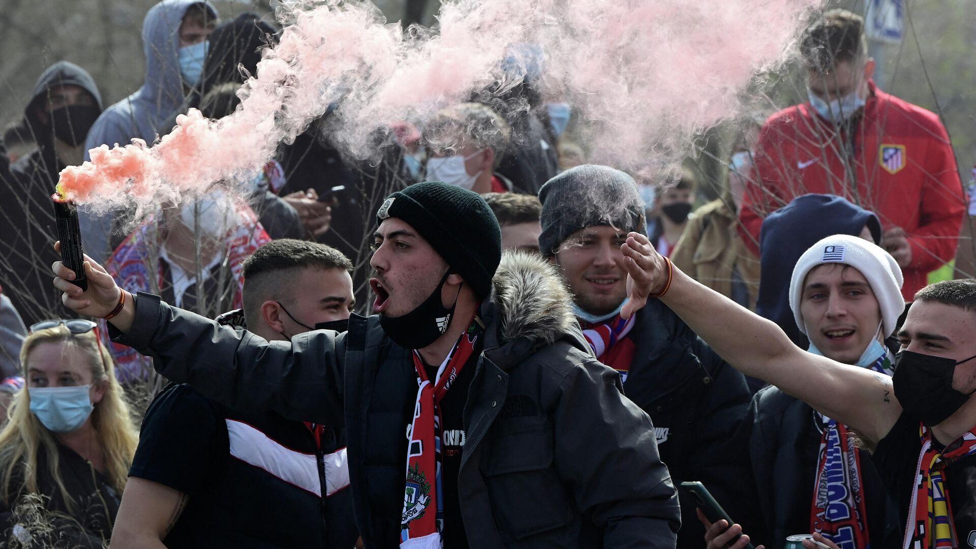 Un aficionado del Atlético enciende una bengala de humo fuera del estadio Wanda Metropolitano de Madrid el 7 de marzo de 2021.  - Sputnik Mundo, 1920, 08.03.2021