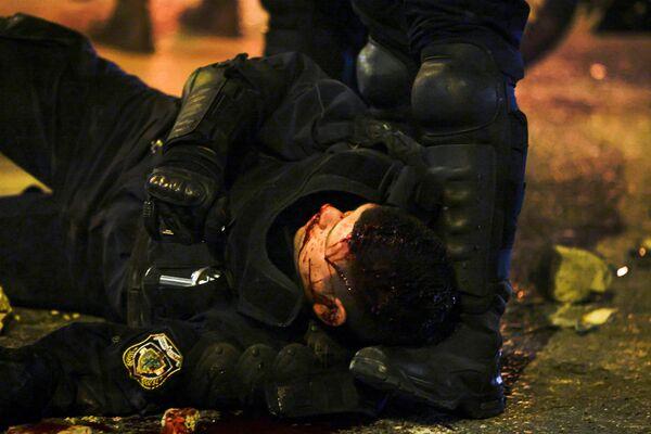 La multitud enfurecida atacó a uno de los policías, lo tiró de su moto y lo golpeó. El agente fue trasladado al hospital con una herida en la cabeza. Varios uniformados también resultaron heridos por la lluvia de piedras y petardos. En la foto: un agente de la Policía herido durante los disturbios en Atenas.   - Sputnik Mundo