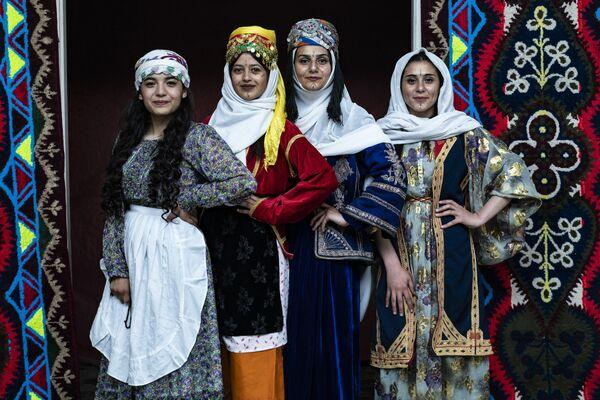 Mujeres kurdas en ropa tradicional posan durante la ceremonia anual de la celebración del Día de la ropa kurda en la ciudad de Qamishli, noreste de Siria. - Sputnik Mundo