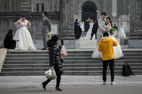 Unos recién casados se sacan fotos junto a la entrada a un templo en Pekín, China. - Sputnik Mundo