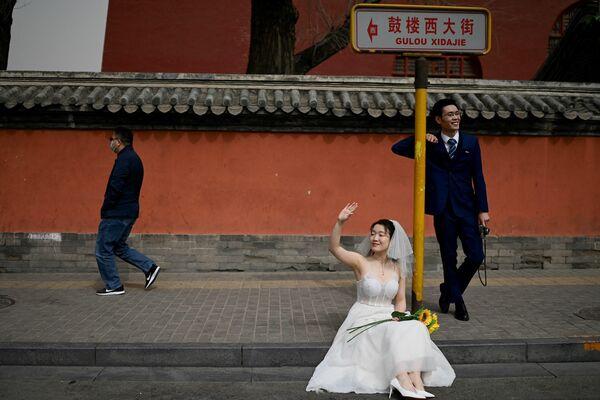 Recién casados durante una sesión de fotos frente a la Torre del Tambor en Pekín, China. - Sputnik Mundo