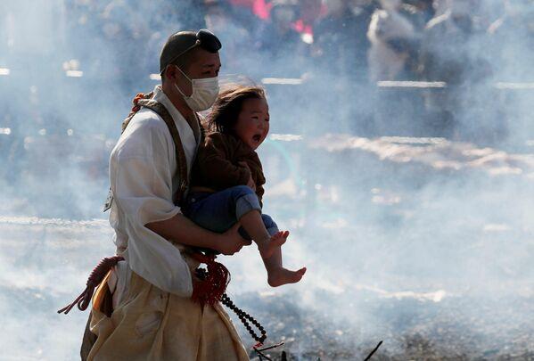 Un monje budista lleva a un bebé que llora en una tradicional caminata sobre brasas ardientes Hiwatari Matsuri en Tokio, Japón. - Sputnik Mundo