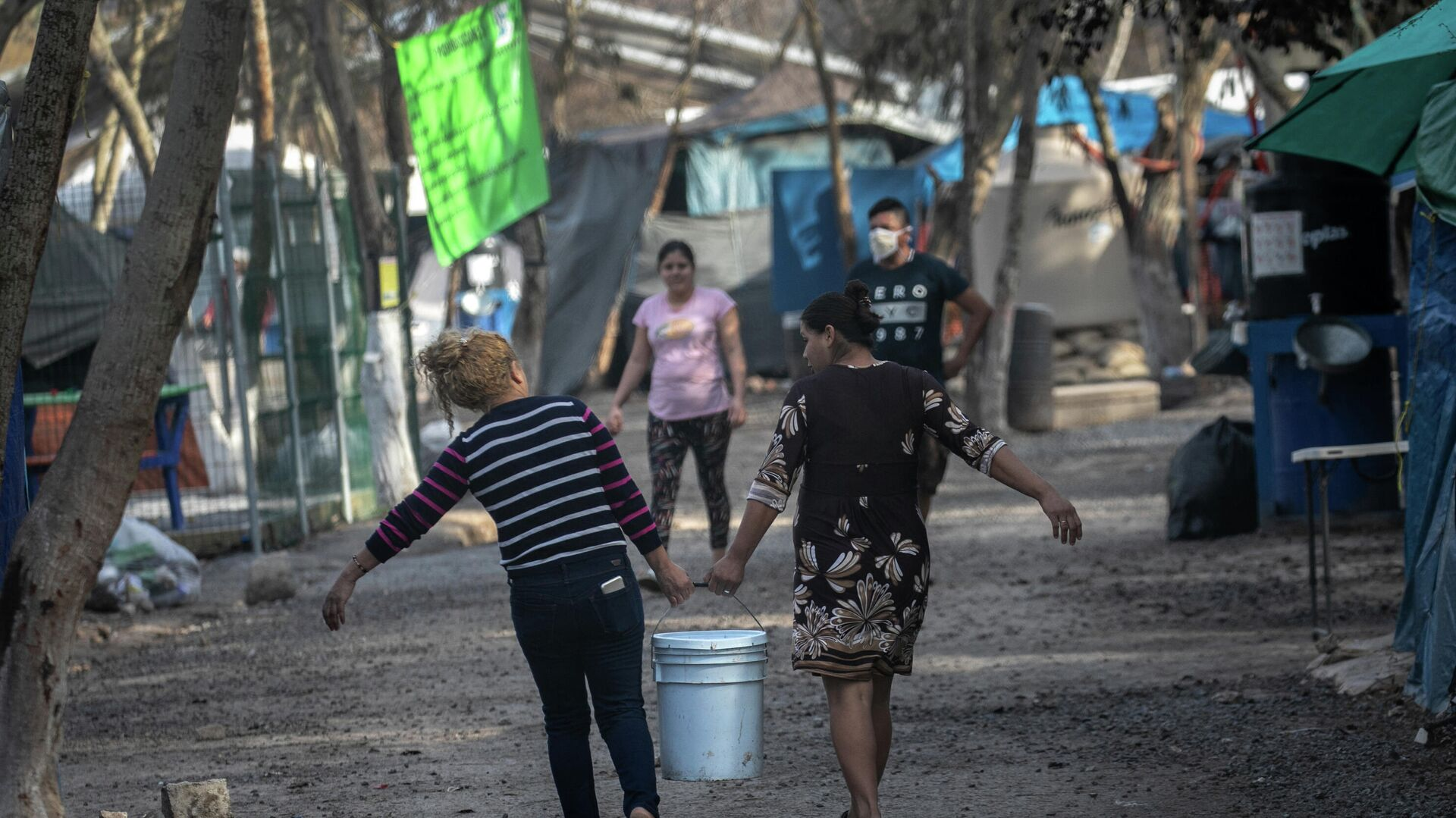 Los solicitantes de asilo en Estados Unidos llevan agua dulce distribuida en un campamento de migrantes en la frontera entre EEUU y México - Sputnik Mundo, 1920, 24.03.2021
