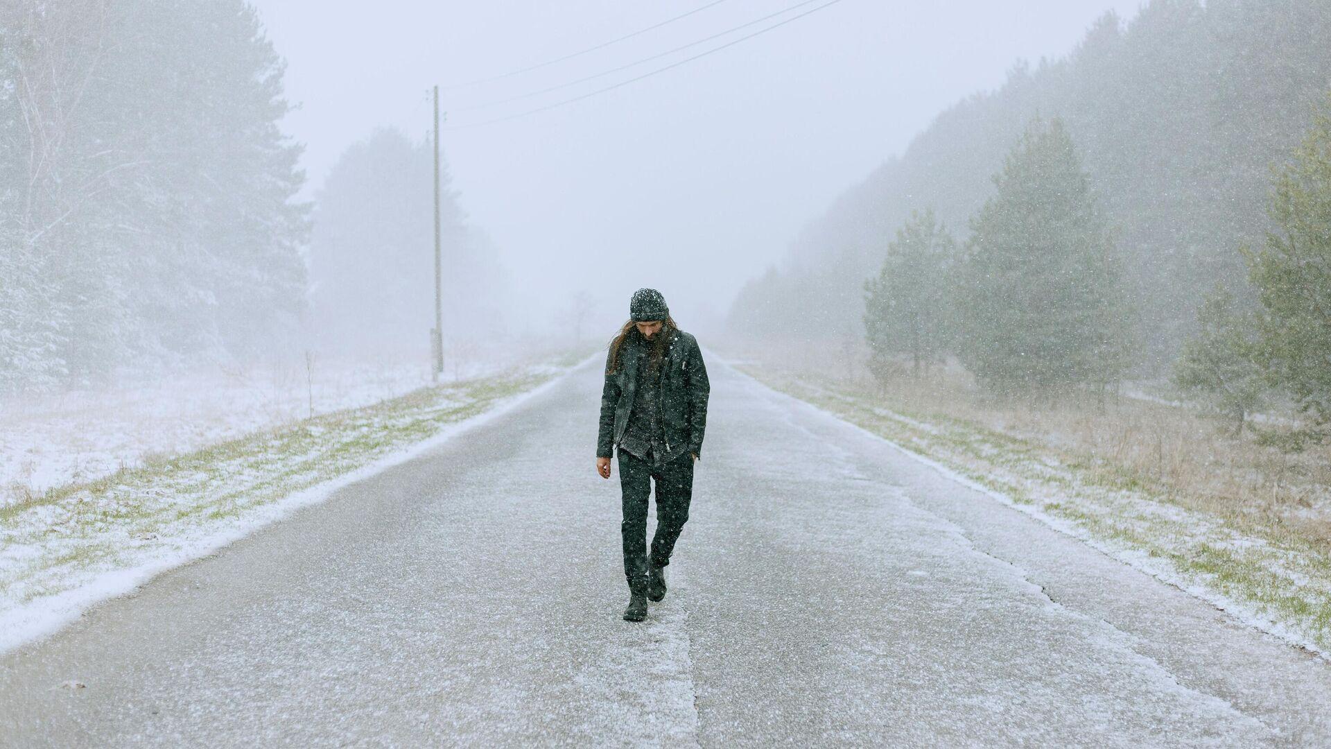 Una persona camina por una calle invernal - Sputnik Mundo, 1920, 25.03.2021