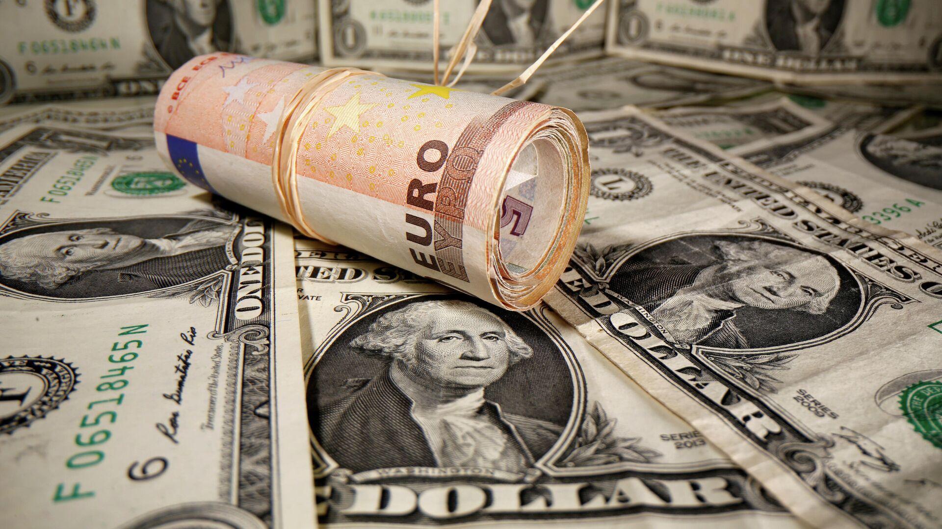 Unos billetes de euro enrollados se colocan sobre unos billetes de dólar - Sputnik Mundo, 1920, 26.03.2021