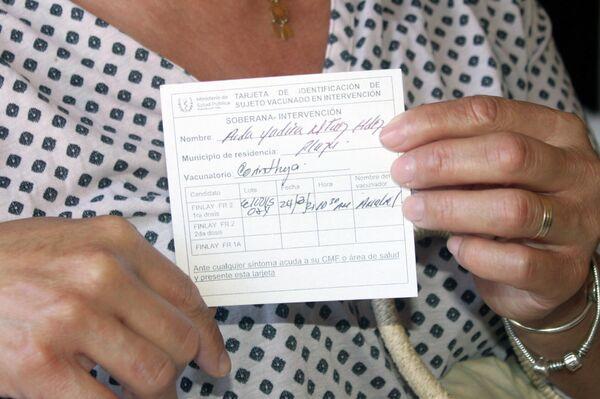 Estomatóloga Aida Martínez  muestra su tarjeta de vacunación - Sputnik Mundo