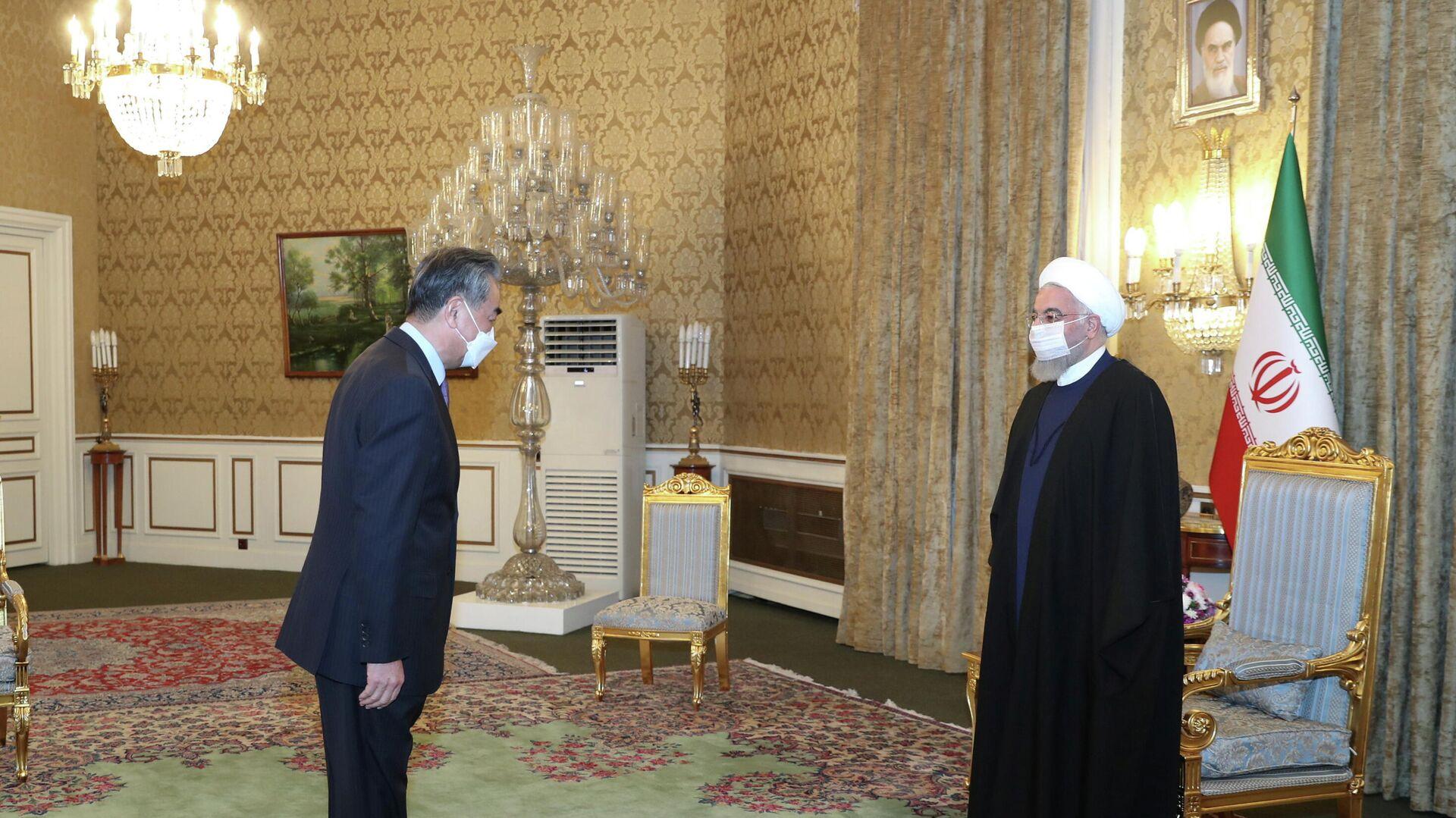 El ministro de Exteriores de China, Wang Yi, y el presidente de Irán, Hasán Rohaní - Sputnik Mundo, 1920, 27.03.2021