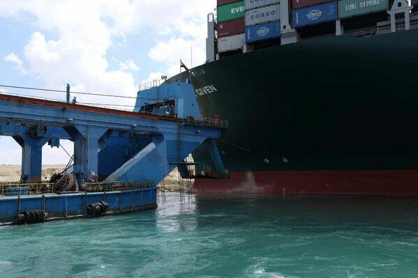 El buque portacontenedores Ever Given con una capacidad de carga de 220.000 toneladas y 400 metros de eslora es uno de los buques de carga más grandes del mundo. En la foto: un remolcador cerca del Ever Given. - Sputnik Mundo
