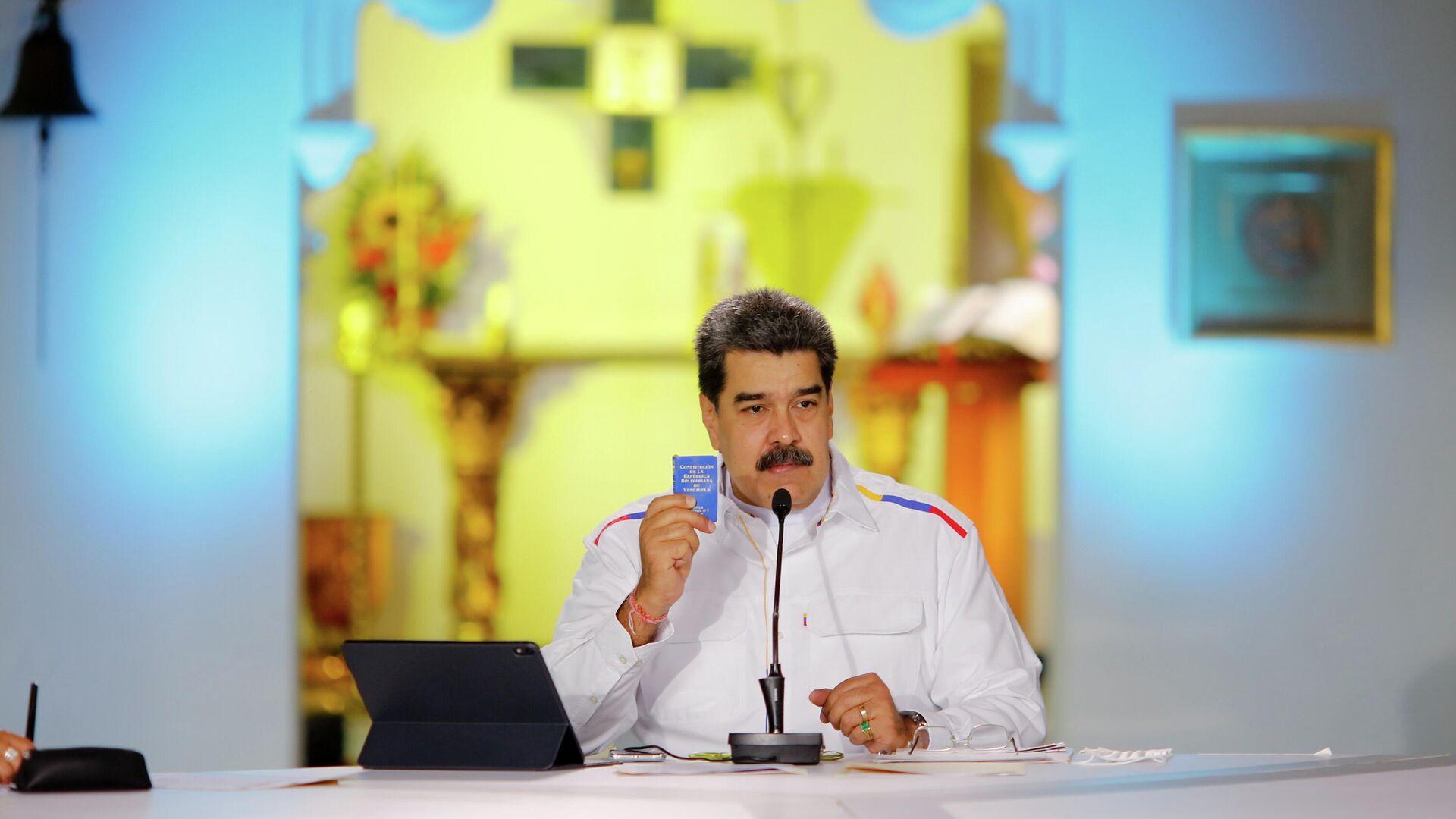 El presidente de Venezuela, Nicolás Maduro, sostiene un ejemplar de la Constitución venezolana durante un discurso en la televisión estatal - Sputnik Mundo, 1920, 29.03.2021