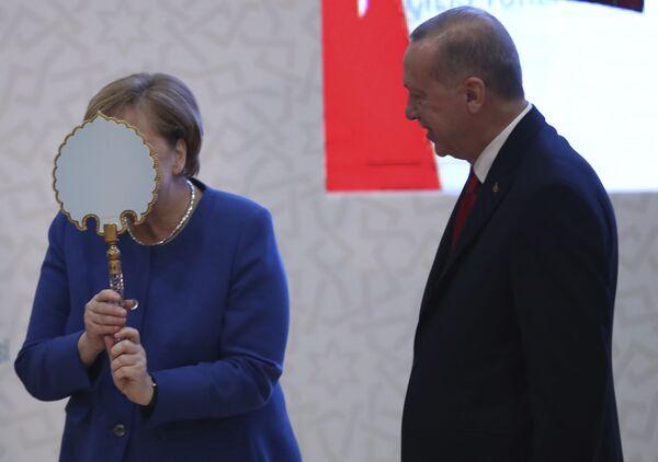 La canciller alemana, Angela Merkel, bromea frente a un espejo que le regaló el presidente turco, Recep Tayyip Erdogan, en Estambul, 2020.  - Sputnik Mundo