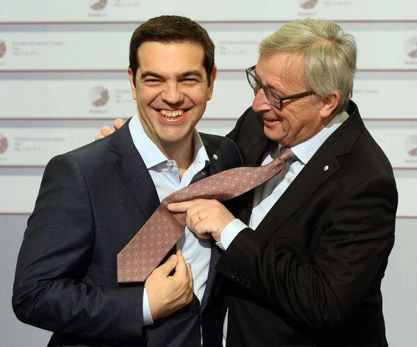 El ex primer ministro griego, Alexis Tsipras, (izquierda) y el expresidente de la Comisión Europea, Jean-Claude Juncker, intercambian bromas sobre sus corbatas en la cumbre de la Asociación Oriental de la UE en Riga (Letonia), 2015. - Sputnik Mundo