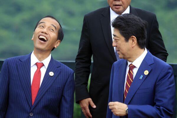 El presidente indonesio, Joko Widodo (izquierda), y el entonces primer ministro japonés, Shinzo Abe, se fotografían para una foto de familia en la cumbre de la APEC en Danang, Vietnam, 2017.  - Sputnik Mundo