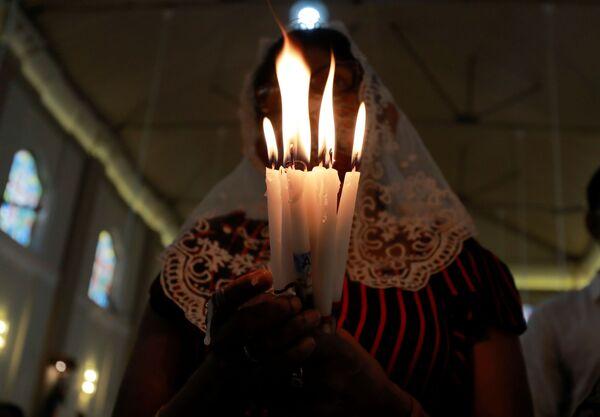 Una creyente asiste a las oraciones del Domingo de Pascua en conmemoración del bombardeo de la Iglesia de San Sebastián el 21 de abril de 2019 en Katuwapitiya (Sri Lanka). - Sputnik Mundo