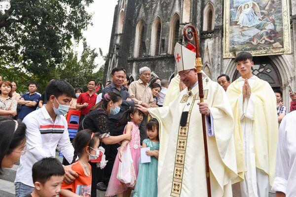 El obispo Joseph Vu Van Thien saluda a los fieles católicos tras celebrar una misa del Domingo de Pascua en la Catedral de San José en Hanói (Vietnam). - Sputnik Mundo