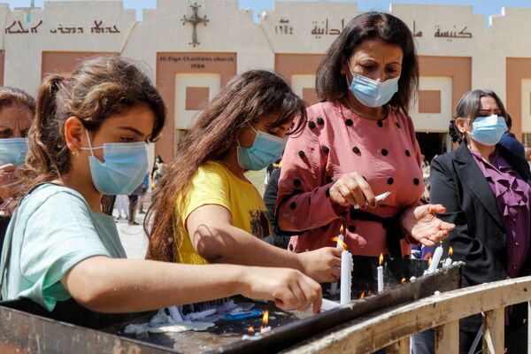 La gente enciende velas para celebrar una misa de Pascua fuera de la Iglesia Caldea de San Elya en medio del brote de coronavirus en Bagdad (Iraq). - Sputnik Mundo