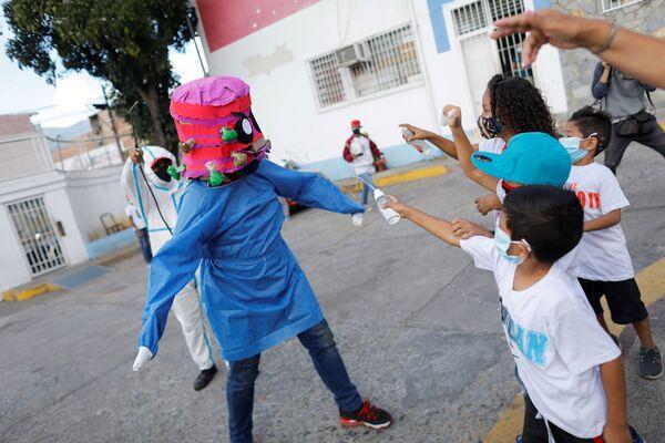 Los niños arrojan alcohol y gel desinfectante de manos contra una persona que lleva una mascarilla que representa el coronavirus durante la quema tradicional de Judas como parte de las celebraciones de Semana Santa en la parroquia de El Cementerio, en Caracas (Venezuela). - Sputnik Mundo
