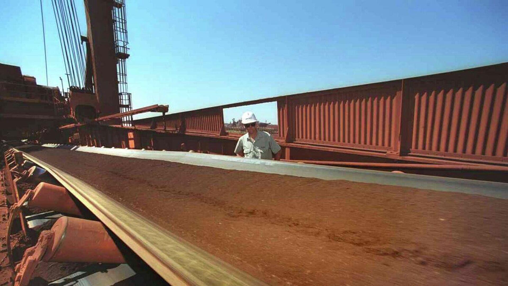 Un trabajador observa una cinta transportadora mientras se extrae mineral de hierro de la Zona Minera C en Pilbara (Australia Occidental) - Sputnik Mundo, 1920, 06.04.2021