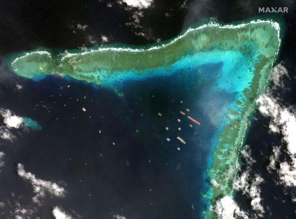 Las embarcaciones pesqueras en el arrecife Whitsun, llamado por Manila arrecife de Julián Felipe, en una imagen satelital de la compañía Maxar tomada el 23 de marzo de 2021. - Sputnik Mundo