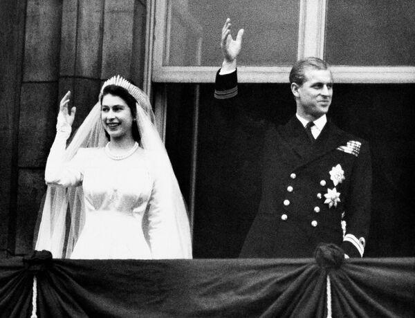 La princesa Isabel y el príncipe Felipe saludan a la multitud desde el balcón del palacio de Buckingham el día de su boda, el 20 de noviembre de 1947. - Sputnik Mundo