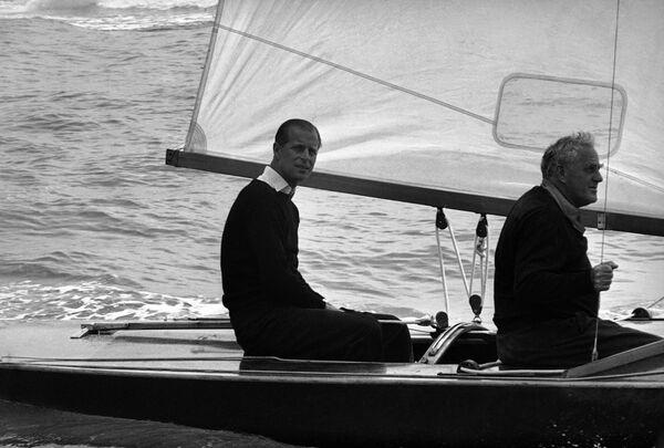 El príncipe Felipe, duque de Edimburgo, al timón del Coweslip, con su compañero de navegación Uffa Fox, antes de la salida de la regata del Royal London Yacht Club, el 6 de agosto de 1963. - Sputnik Mundo