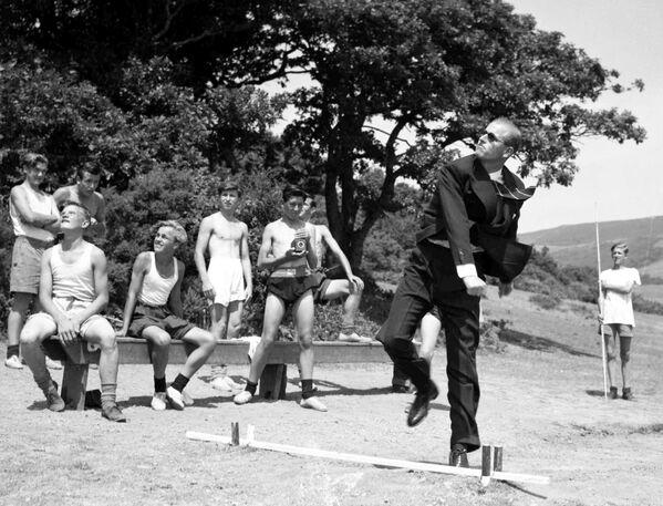 El príncipe Felipe lanza una jabalina durante la visita al Outward Bound Sea School, en Gales, el 12 de julio de 1949. - Sputnik Mundo