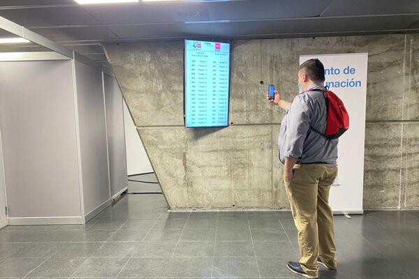 Un hombre dentro del WiZink Center de Madrid fotografía la pantalla donde aparecen los turnos para vacunarse - Sputnik Mundo
