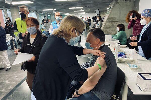 Un hombre se vacuna con la AstraZeneca en el WiZink Center de Madrid - Sputnik Mundo