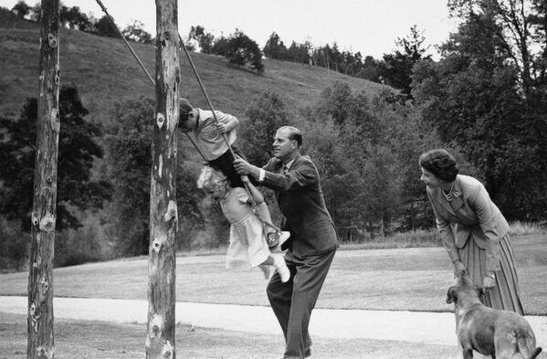 El duque de Edimburgo balancea a sus hijos, el príncipe Carlos y la princesa Ana, en un columpio en el castillo de Balmoral (agosto de 1955). - Sputnik Mundo