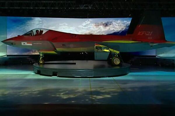 Caza KF-21 con proyecciones de distintas banderas sobre su fuselaje durante su presentación oficial.  - Sputnik Mundo