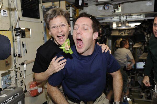 El astronauta francés Thomas Pesquet y la astronauta de la NASA Peggy Whitson a bordo de la EEI con una hoja de lechuga.   - Sputnik Mundo