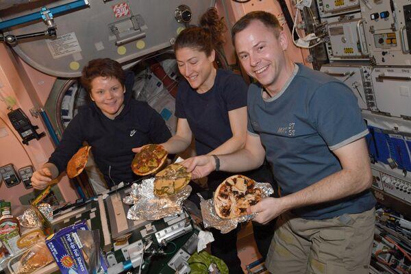 """El astronauta estadounidense Nick Hague (a la derecha) compartió en su cuenta de Twitter una imagen de una espontánea fiesta de pizza en la EEI. """"Hacer pizza en el espacio es similar a hacer pizza en la Tierra, la única diferencia es que nuestros hornos son un poco diferentes y nuestra pizza puede flotar"""", explicó.  - Sputnik Mundo"""