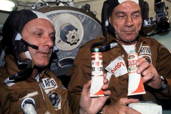 Astronautas Thomas P. Stafford y Donald K. 'Deke' Slayton con bolsas de alimentos espaciales soviéticos en el módulo orbital Soyuz durante la misión conjunta de acoplamiento en órbita terrestre del Proyecto de Prueba Apolo-Soyuz de EEUU y la URSS. En los tubos se lee 'vodka' aunque son etiquetas falsas pegadas de broma para brindar. De hecho, dentro de los tubos hay borsch, una sopa tradicional de remolacha.  - Sputnik Mundo