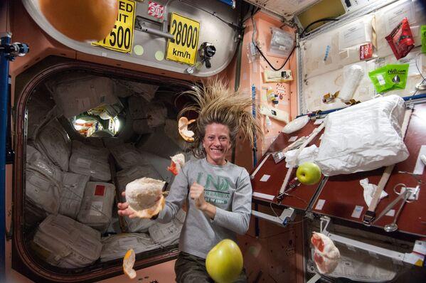 La astronauta de la NASA Karen Nyberg, ingeniera de vuelo de la Expedición 36, cerca de la fruta fresca que flota libremente en el nodo Unity de la Estación Espacial Internacional.  - Sputnik Mundo
