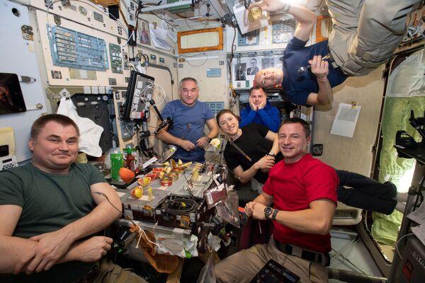 Los seis miembros de la expedición 60 comen fruta fresca y platos enlatados y preenvasados.  - Sputnik Mundo