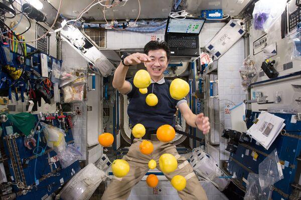 El astronauta japonés Kimiya Yui recoge fruta voladora que fueron enviados a la EEI en una nave de carga Kounotori 5 H-II Transfer Vehicle (HTV-5).  - Sputnik Mundo