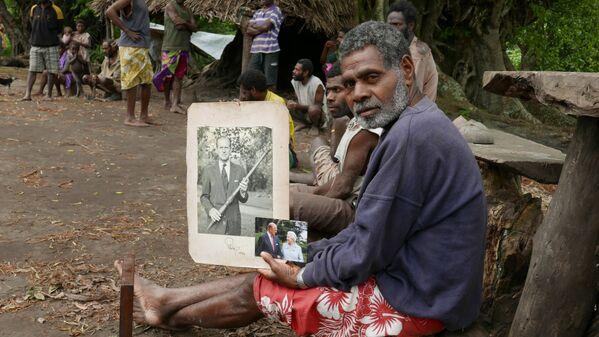 El jefe de la aldea Jack Malia con unas fotos del fallecido príncipe Felipe y de la reina Isabel en las manos el 6 de mayo de 2017 en Yaohnanen, en la isla de Tanna. - Sputnik Mundo